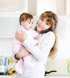 Woman on the phone while holding her baby in her arms in the kit Stock Photography