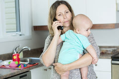 Woman on the phone while holding her baby in her Stock Photos