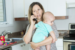 Woman on the phone while holding her baby in her Royalty Free Stock Photography