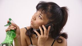 Woman on the phone holds spray bottle Stock Photo