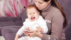 the woman on the phone, ignores the crying child. stock image