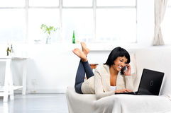 Woman with phone and laptop Stock Photo