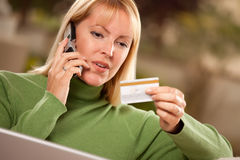 Woman on Phone and Laptop with Credit Card Royalty Free Stock Image