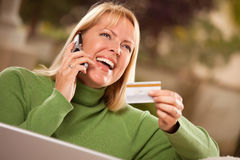 Woman on Phone and Laptop with Credit Card Stock Photo