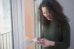 Woman with phone. Latin woman chating with her mobile phone next to a window at home Royalty Free Stock Image