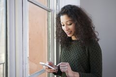 Woman with phone. Latin woman chating with her mobile phone next to a window at home Stock Image
