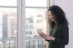 Woman with phone. Latin woman chating with her mobile phone next to a window at home Royalty Free Stock Photos