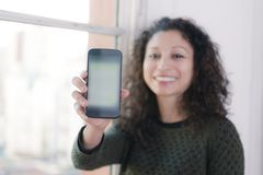 Woman with phone. Latin woman showing us a mobile phone Royalty Free Stock Image