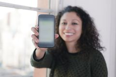 Woman with phone. Latin woman showing us a mobile phone Royalty Free Stock Images
