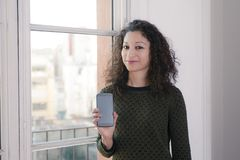 Woman with phone. Latin woman showing us a mobile phone Royalty Free Stock Photos
