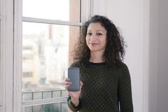 Woman with phone. Latin woman showing us a mobile phone Stock Photos