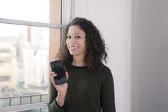 Woman with phone. Latin woman showing us a mobile phone Stock Images