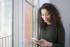 Woman with phone. Latin woman chating with her mobile phone next to a window at home Stock Photo