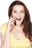 Woman on the phone laughing. A beautiful young woman on her mobile phone and laughing on a white background Royalty Free Stock Image