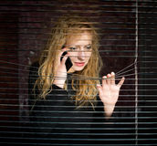 Woman on the phone looking through venetian blinds Stock Images