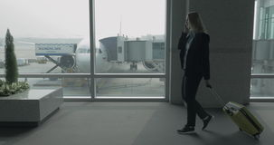 Woman with phone and luggage walking in Seoul airport, South Korea stock footage