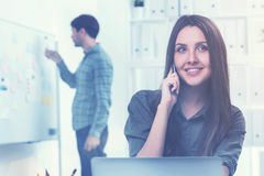 Woman on the phone and a man in office Royalty Free Stock Photos