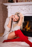 Woman with phone near fireplace Royalty Free Stock Image