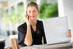 Woman with Phone and Newspapers Royalty Free Stock Photography