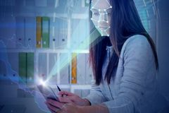 Woman with phone in office, face recognition graph. Young businesswoman working with smartphone in office. Phone with face recognition technology, HUD interface royalty free stock photos