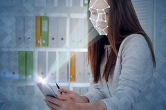 Woman with phone in office, face recognition. Young businesswoman working with smartphone in office. Phone with camera and face recognition technology. Toned stock photo