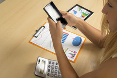 Woman with phone in office. Young woman working with charts , calculator and phone in office royalty free stock photo