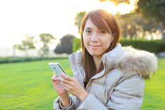 Woman with phone outdoors Stock Image