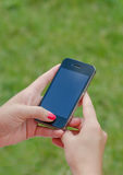 Woman with phone outside. Green grass, sunny day Royalty Free Stock Photography