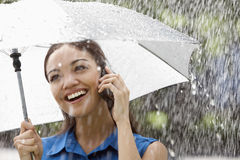 Woman on the phone in the rain. Beautiful Hispanic woman holding umbrella out in the rain talking on a cell phone Stock Photos