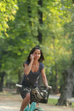 Woman on the phone riding bicycle Stock Images