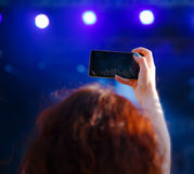Woman with phone shooting concert, view from behind, blur effect stock photo