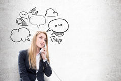 Woman on phone and speech bubbles. Portrait of a blond businesswoman talking on the phone while sitting near a concrete wall with speech bubbles drawn on it Royalty Free Stock Image