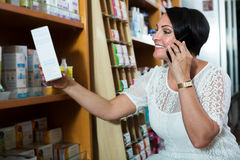 Woman with phone in store Stock Photography