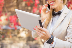Woman on the phone with tablet in her hand. Close up of woman on the phone with tablet in her hand Royalty Free Stock Image