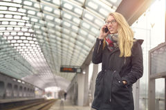 Woman on phone at train station platform Royalty Free Stock Photography