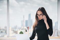 Woman on phone using laptop Royalty Free Stock Photo
