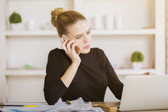 Woman on phone using laptop Royalty Free Stock Images