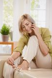 Woman on phone using nail polish. Smiling woman talking on mobile phone while using nail polish on toes sitting on couch at home stock image