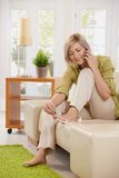 Woman on phone using nail polish Stock Images
