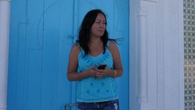 Woman with phone waiting somebody near blue arabian door. Attractive brunette woman in blue clothing stock footage