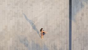 The woman with phone walk on pedestrian with black silhouette shadow. Woman with phone walk on pedestrian with black silhouette shadow on ground top aerial view royalty free stock photo