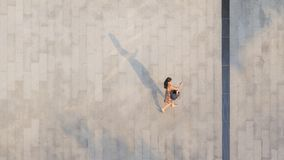 The woman with phone walk on pedestrian with black silhouette shadow. Woman with phone walk on pedestrian with black silhouette shadow on ground top aerial view stock image