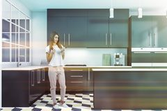 Woman with phone in white and gray kitchen royalty free stock photo