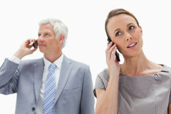 A woman on the phone with a white hair businessman. Close-up of a women on the phone with a white hair businessman in background Stock Image
