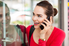 Woman on phone window shopping. A beautiful happy woman is talking on the phone and looking in a shop window stock images