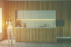 Woman with phone in wooden kitchen with bar. Young woman with phone standing in modern kitchen interior with wooden countertops and cupboards and island with royalty free stock image