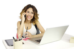 Woman on the phone while working with computer Stock Images