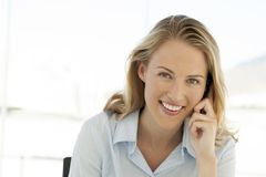 Woman on the phone at workplace - using mobile phone royalty free stock photography