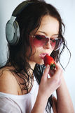 Woman in phones. Happy woman dance in phones and eat strawberry Royalty Free Stock Photos