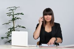 Woman phones at the desk Royalty Free Stock Photo